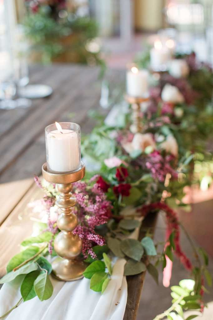 low floral and candle arrangement the length of a long wooden table consisting of white candles on top of gold pillars with greenery