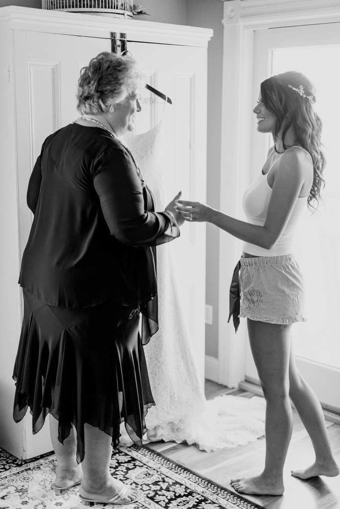 a black and white candid photo of the bride in shorts and a tank top with her mother admiring her gown hanging up