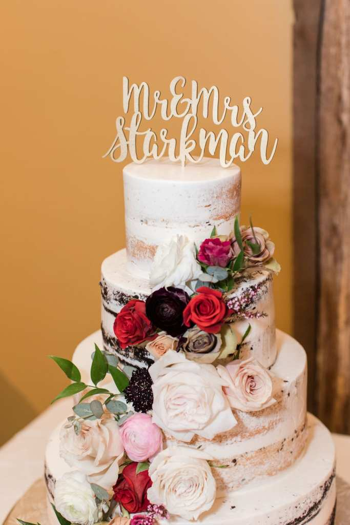 Formal photo of the four tier semi-naked wedding cake by Conroy Catering with rose accents in shades of reds, pinks, and creams, with a custom gold cake topper with the new couples name