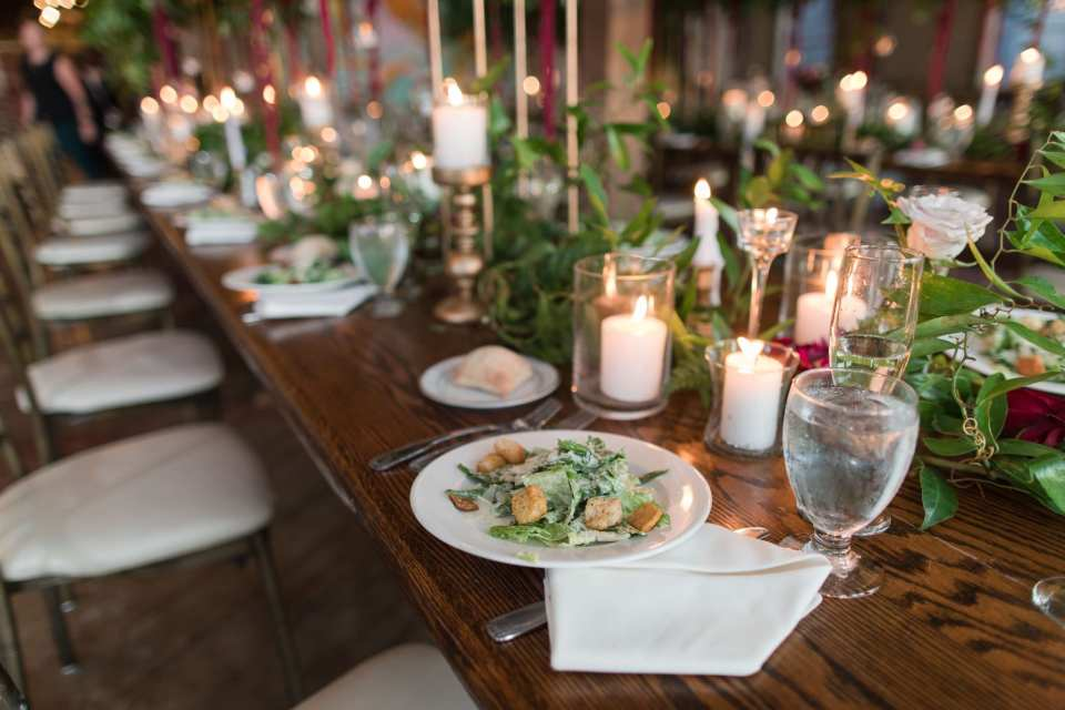 detail shot of the salad course at Laurita Winery, candles and greenery down the middle of the table