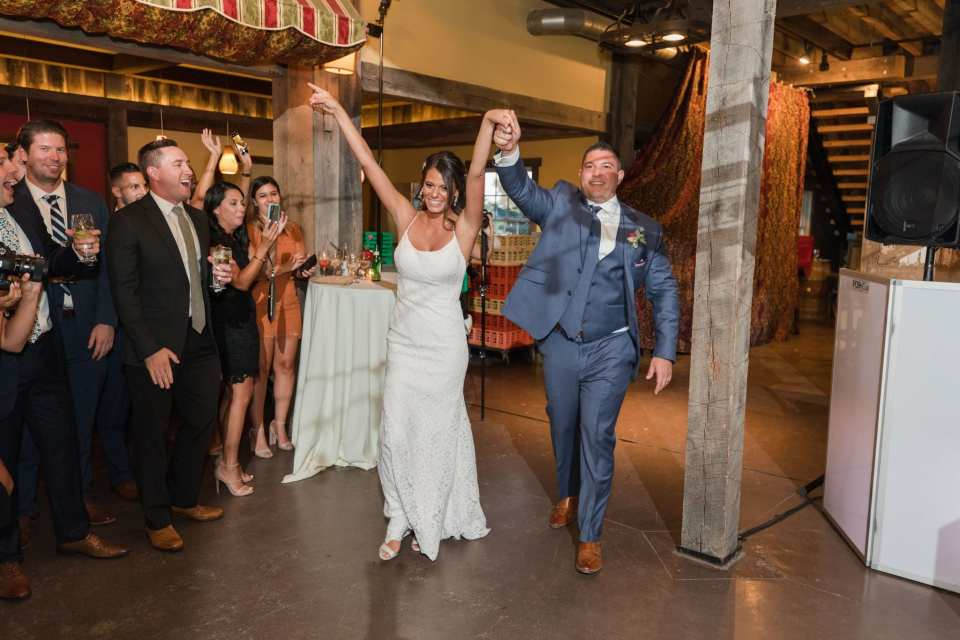 The bride and groom make their entrance into the wedding reception with arms raised