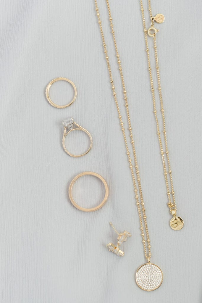 Close up of the brides jewelry for the day consisting of gold necklaces, earrings and rings