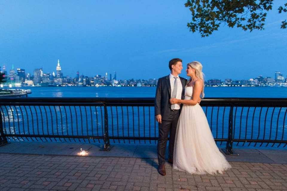 The bride and groom looking at each other, in one another's arms, outside the W Hotel Hoboken with the New York City skyline in the background, at dusk