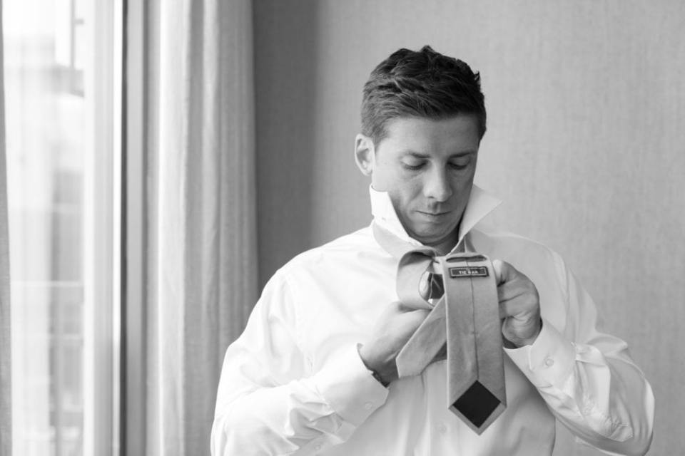 Black and white photo of the groom putting on his tie