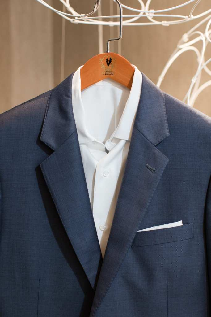The grooms blue suit on a wooden hanger