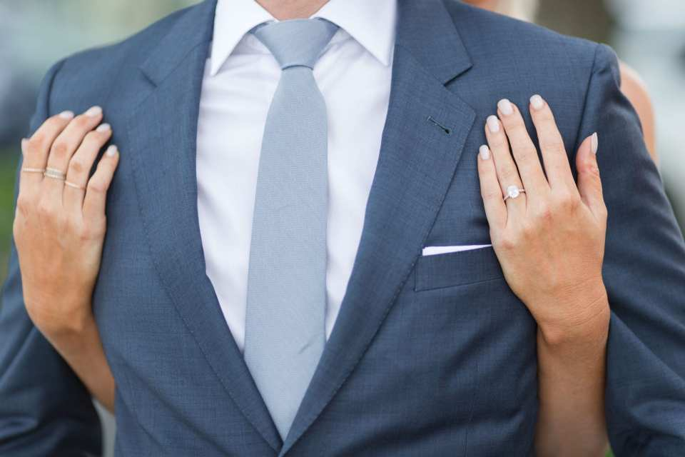 Photo of the groom's chest, with the brides hands under his arms from behind, her hands resting on his chest, clearly showing her oval diamond solitaire ring along with stacking rings on her right hand
