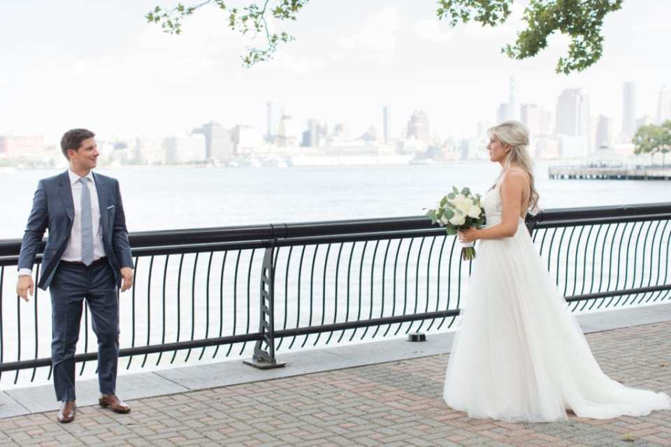 The groom turns to see his bride during their first look on the waterfront outside the W Hotel Hoboken, the New York City skyline in the background