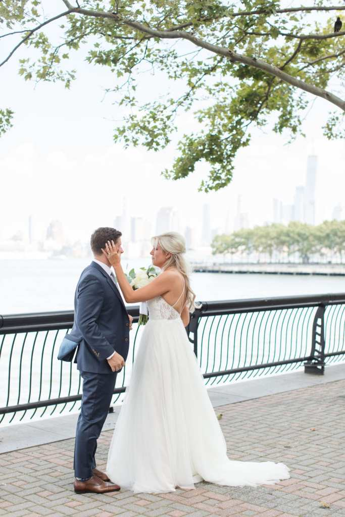 A candid of the bride and groom during their first look outside the W Hotel Hoboken, on the waterfront, with the New York City skyline in the distance. The brides hand is on her grooms face.