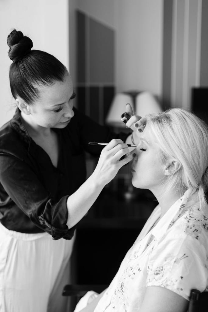 Black and white photo of the brides makeup being applied