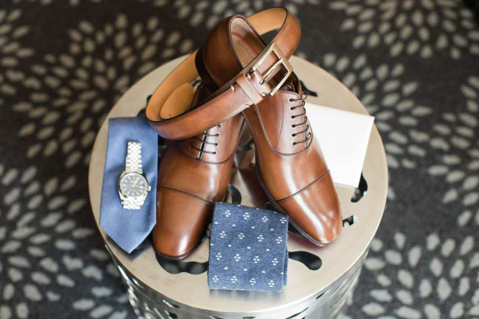 Grooms details including a brown belt with matching shoes, his colonial blue tie, watch