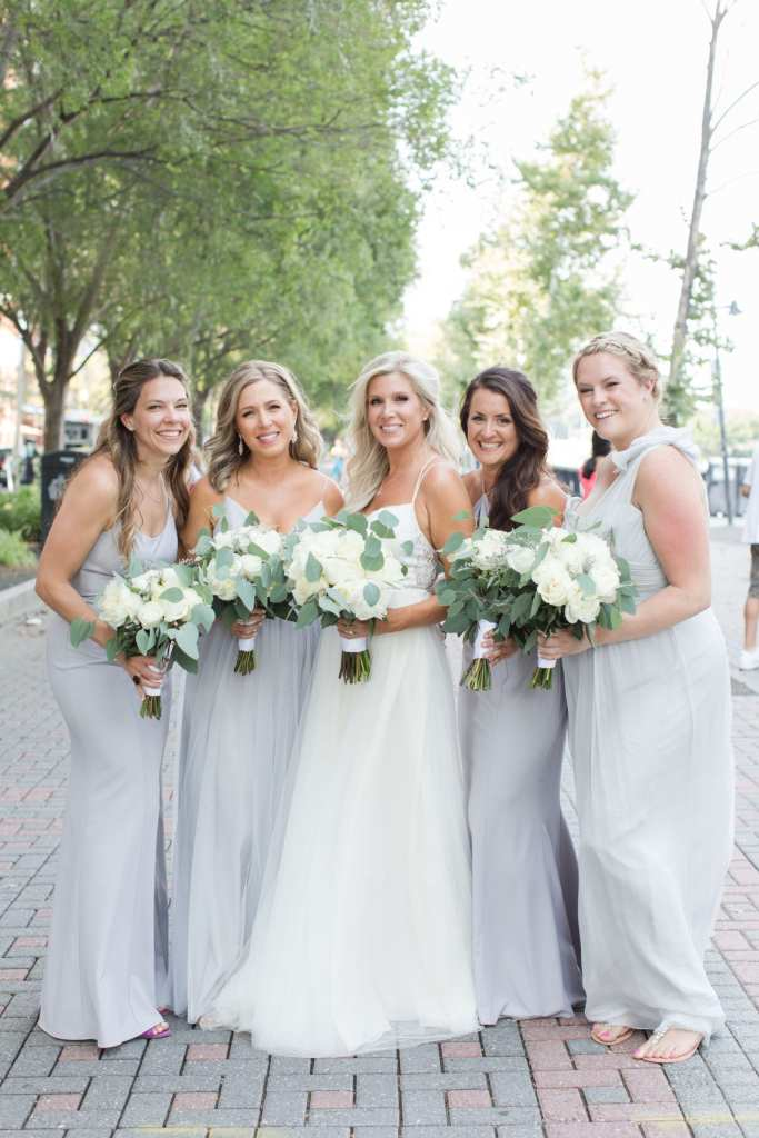Bride with her bridal party in pale blue gowns holding their bouquets of white florals with a few greens