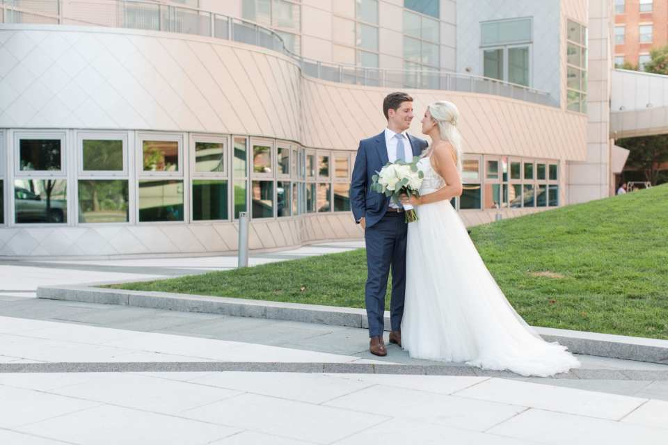 Bride and groom in each others arms, looking at one another, the bride holding her bouquet, outside the W Hotel Hoboken