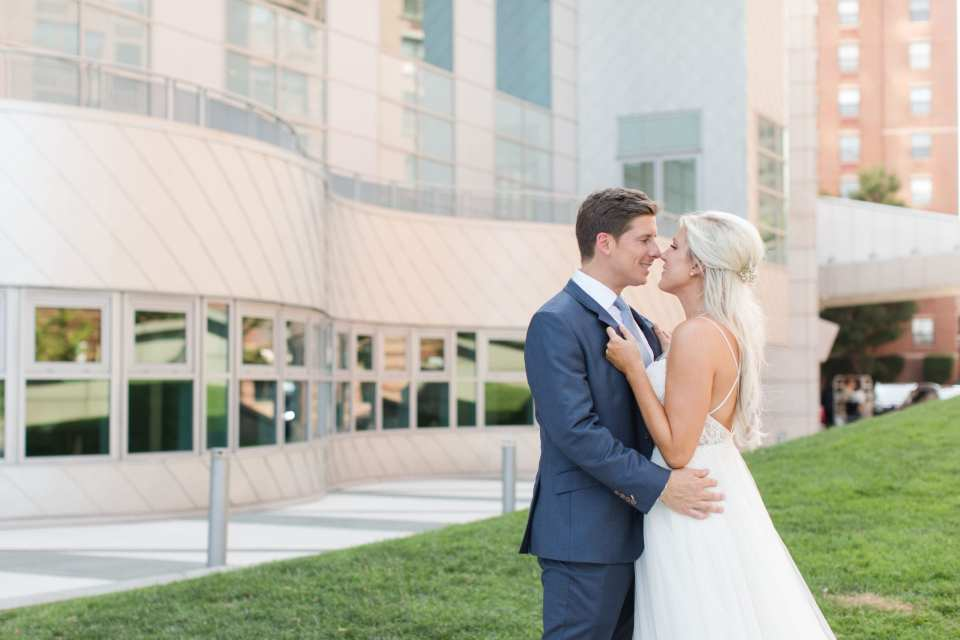 Bride and groom in each others arms, looking at one another, outside the W Hotel Hoboken
