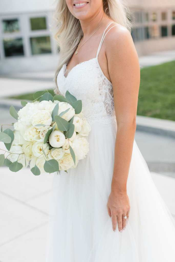 3/4 portrait of bride in gown holding bridal bouquet of off white florals and a few greens