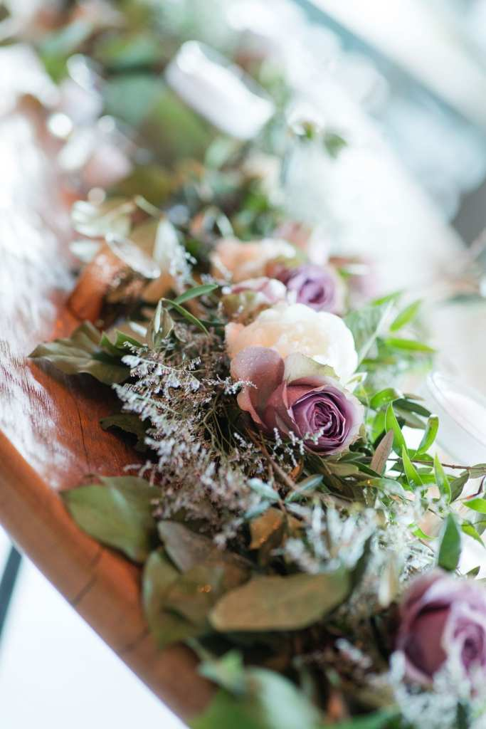 Floating candle, greenery and roses in shades of light purple and white on a wooden table