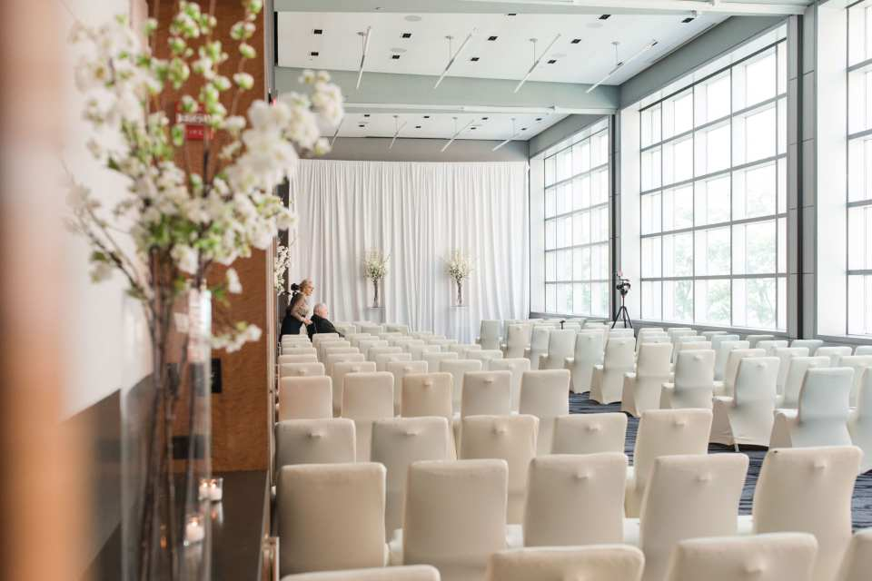 The ceremony room inside the W Hotel Hoboken with full wall of windows, the altar wall draped in white fabric and the chairs covered in white fabric. Tall floral arrangements in clear glass vases with white florals around the room