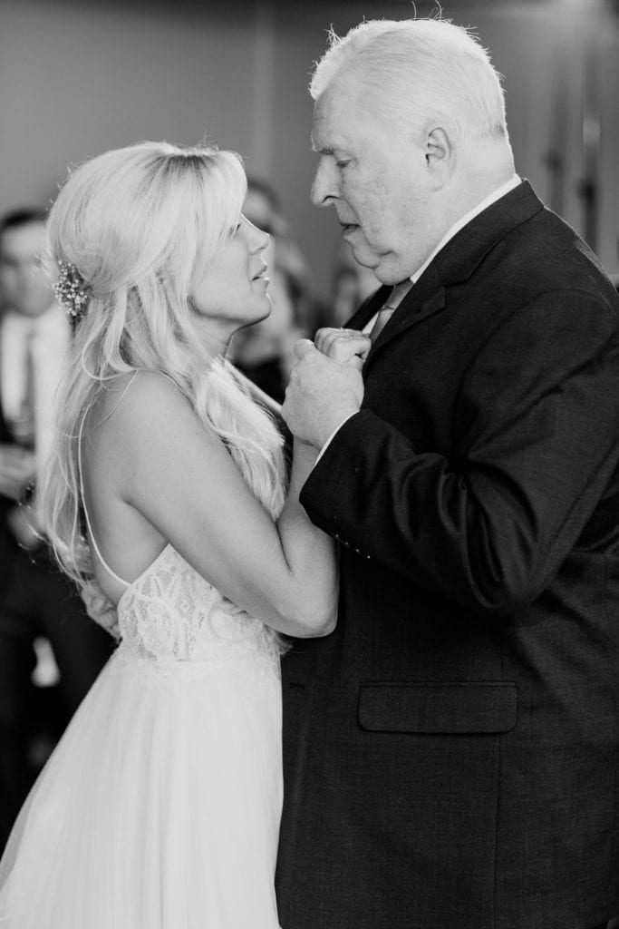 Black and white photo of the bride dancing with her father