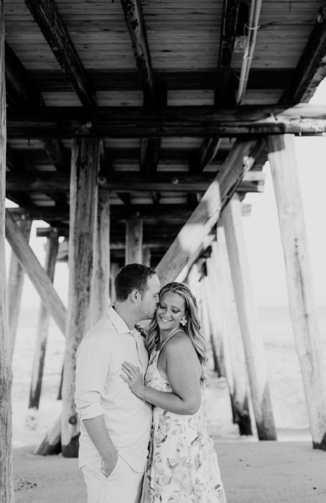 Black and white photo of couple under the boardwalk, she is looking down at the sand, towards the camera, he is kissing her cheek