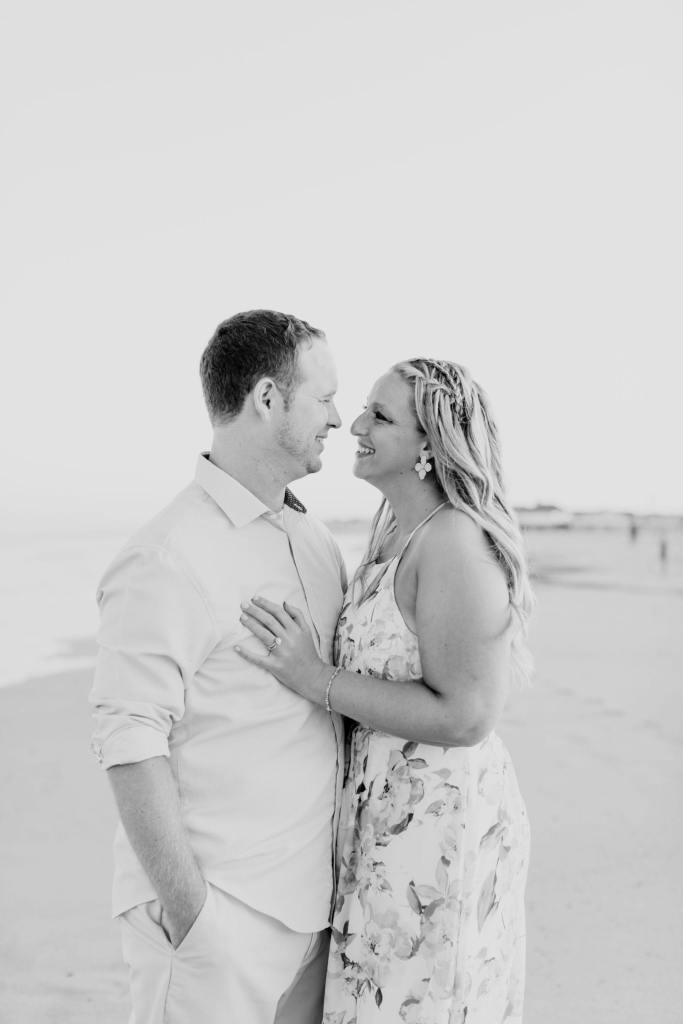 black and white photo of couple gazing into each other's eyes while standing on the beach