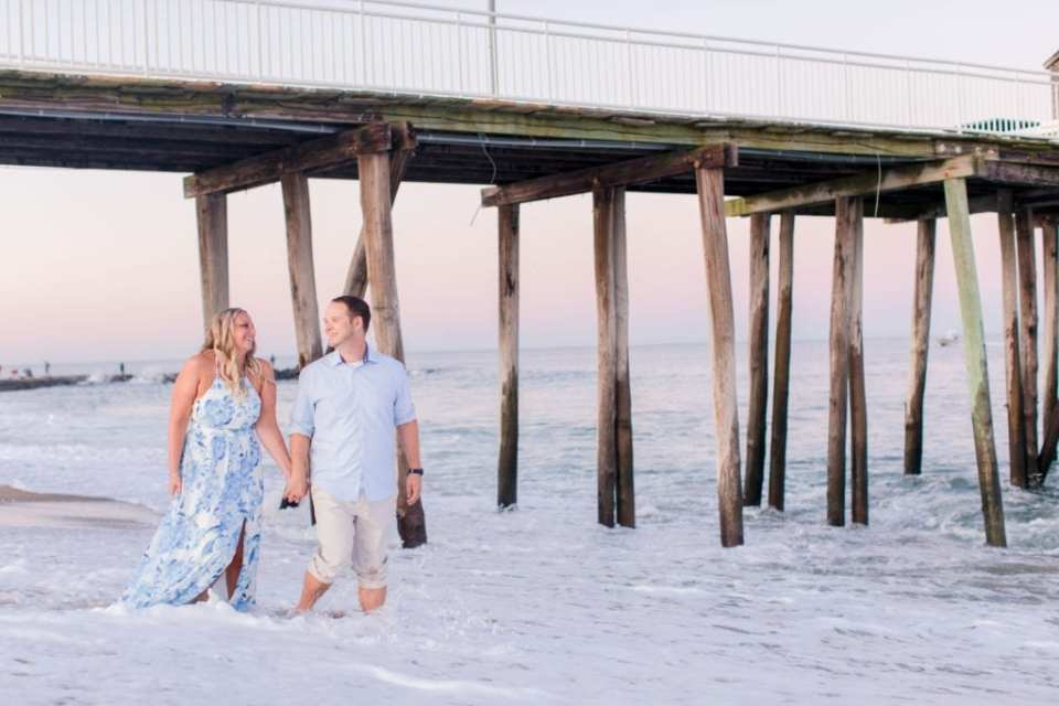 Bride to be in a blue patterned maxi dress by Morgan and Co. from Macy's, groom to be in a classic blue oxford button down and rolled up khaki pants walking hand in hand through the surf