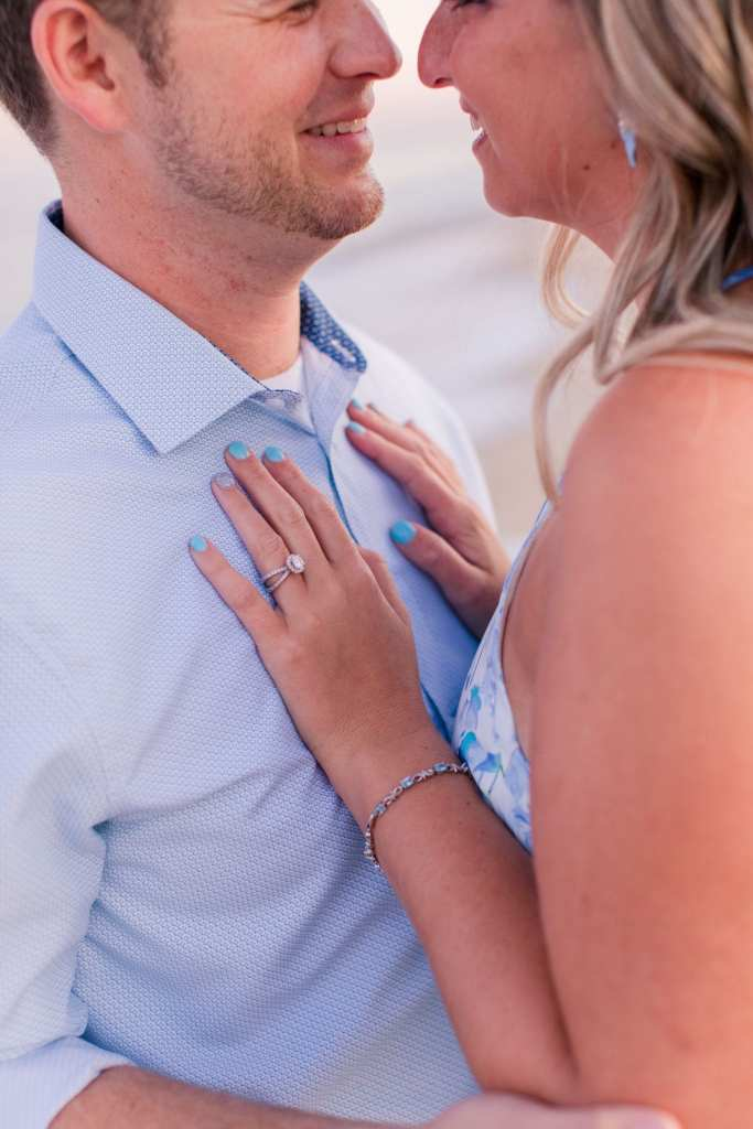 bride to be's hands on the chest of her future husband, focus on her left hand with her diamond engagement ring on it.