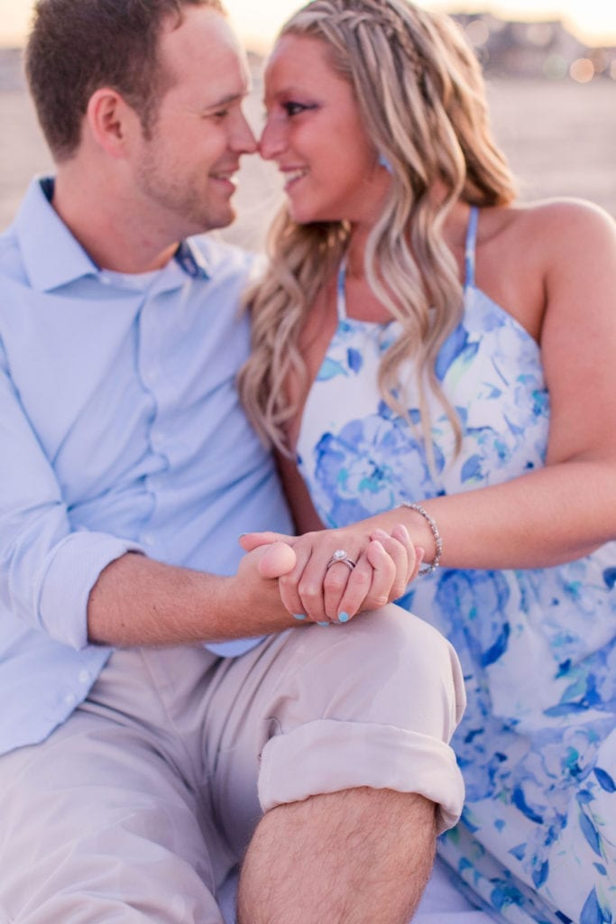 engaged couple, her in a blue and white patterned halter dress, he in a blue oxford button down shirt sitting next to one another on the beach, his right hand holding her left hand, showing off her diamond engagement ring by Ocean of Diamonds