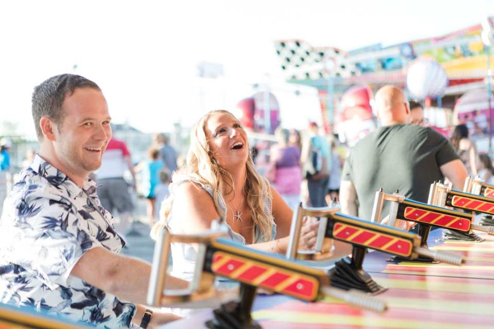 Couple laughs while playing a boardwalk game on Jenkinson's Pavilion during their engagement session