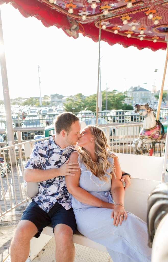 engaged couple ride the carousel together on Jenkinson's Pavilion, kissing while sitting in a chair on the ride, the round diamond engagement ring from Oceans of Diamonds on display