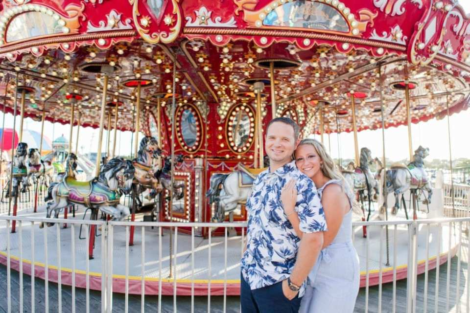 Bride to be behind her groom to be, arms under his, both smiling at the camera, in front of the carousel at Jenkinson's Pavilion, Point Pleasant by Jaye Kogut Photography, New Jersey Wedding photographer