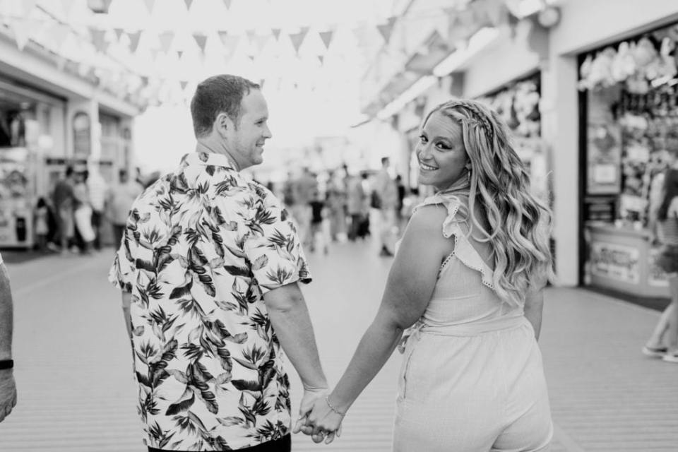 Black and white photo of couple walking away from the camera, groom to be looking at his bride to be, whom is looking back at the camera. On the boardwalk at Jenkinson's Pavilion, Point Pleasant.