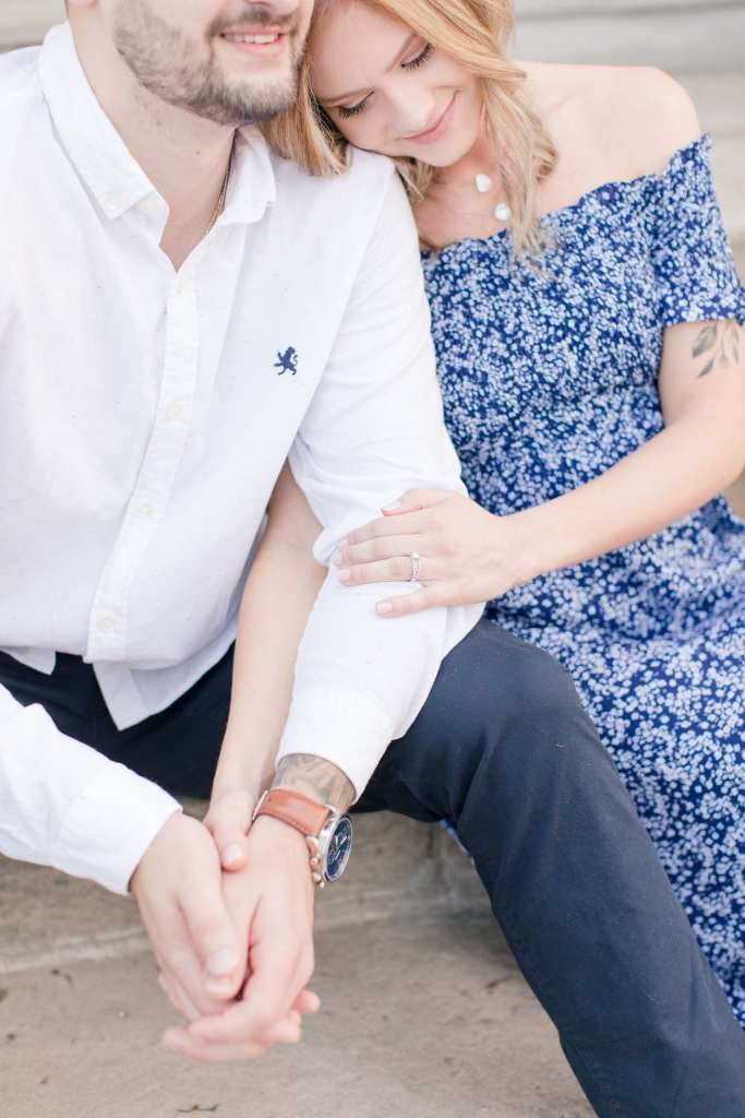 Groom to be in white button down shirt, sitting next to his bride to be in a blue patterened off the shoulder dress, engagement ring in focus