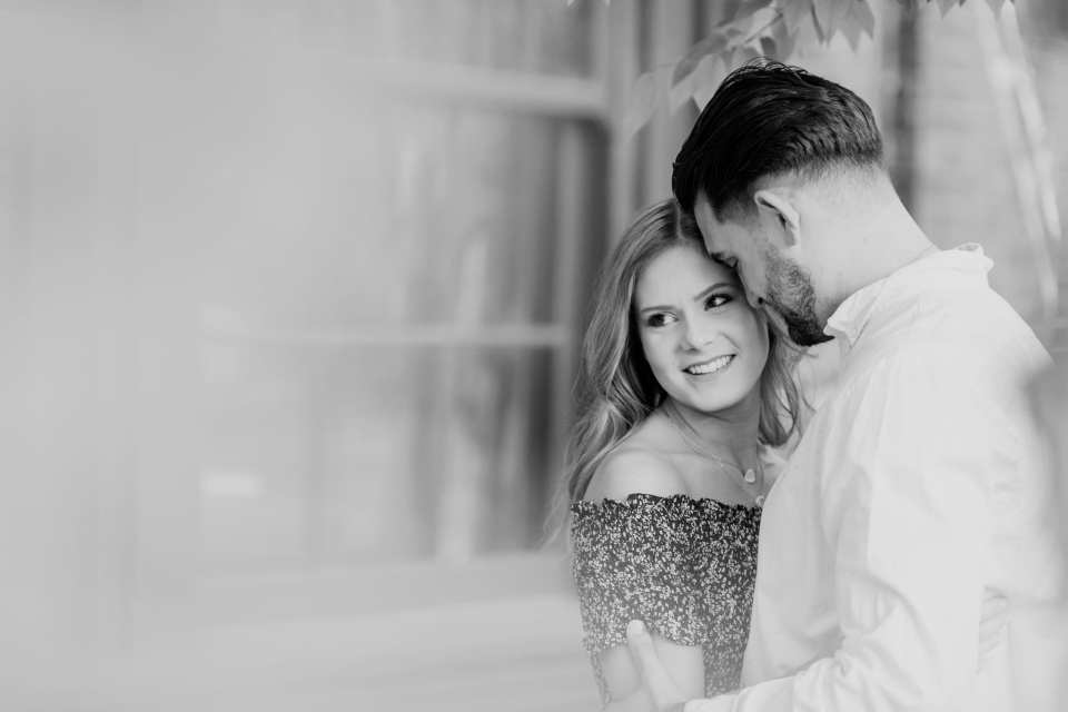Black and white photo of the engaged couple embracing, photo shot through the trees