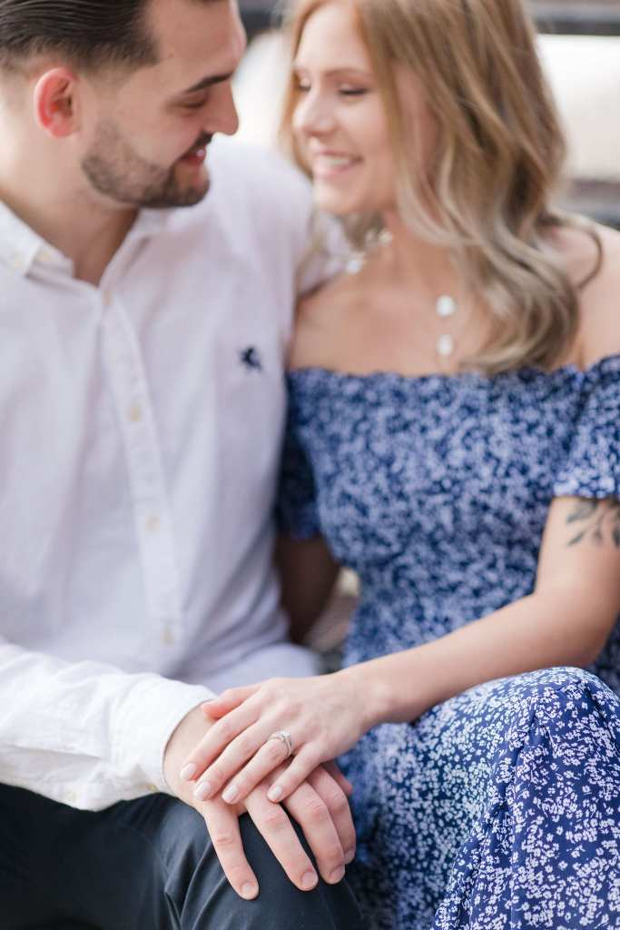 Groom to be in white button down shirt, sitting next to his bride to be in a blue patterened off the shoulder dress, her left hand on his right hand, on his left knee, engagement ring in focus
