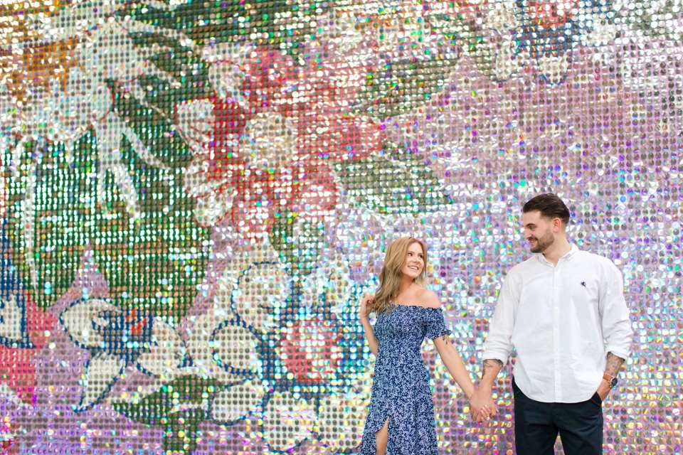 Engaged couple walking, the bride to be in blue print dress and leading her groom to be, in front of floral textured wall at the Philadelphia Navy Yard.