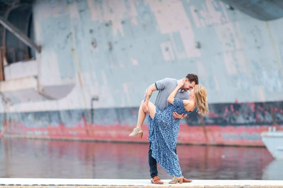 Groom to be dipping his bride to be in front of a ship at the Philadelphia Navy Yard by New Jersey engagement photographer