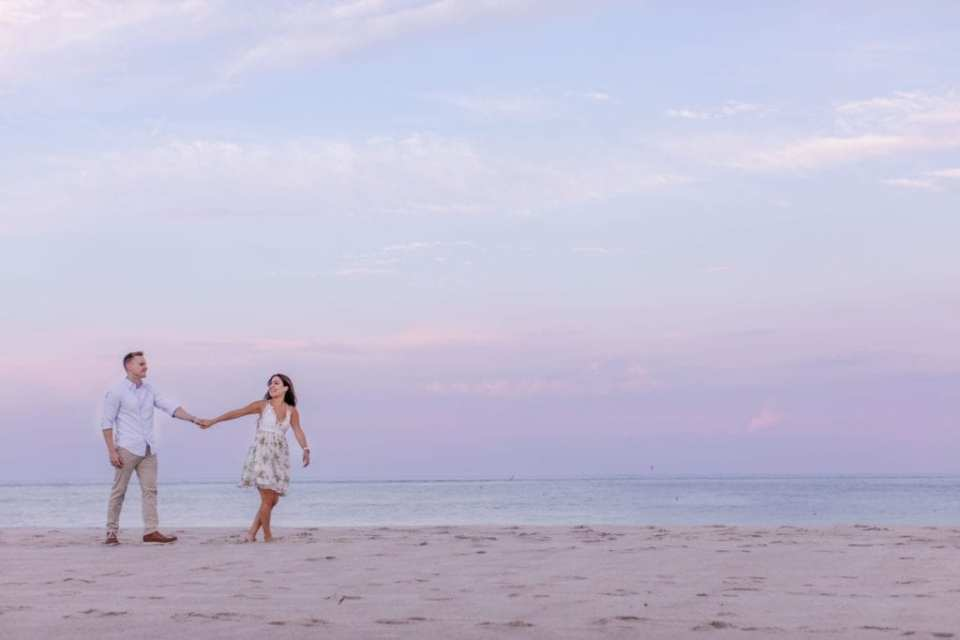 Sunset shot with purple and blue sky behind the bride and groom to be walking on the beach by New Jersey engagement photographer. Bride to be dress by Ruby and Jenna