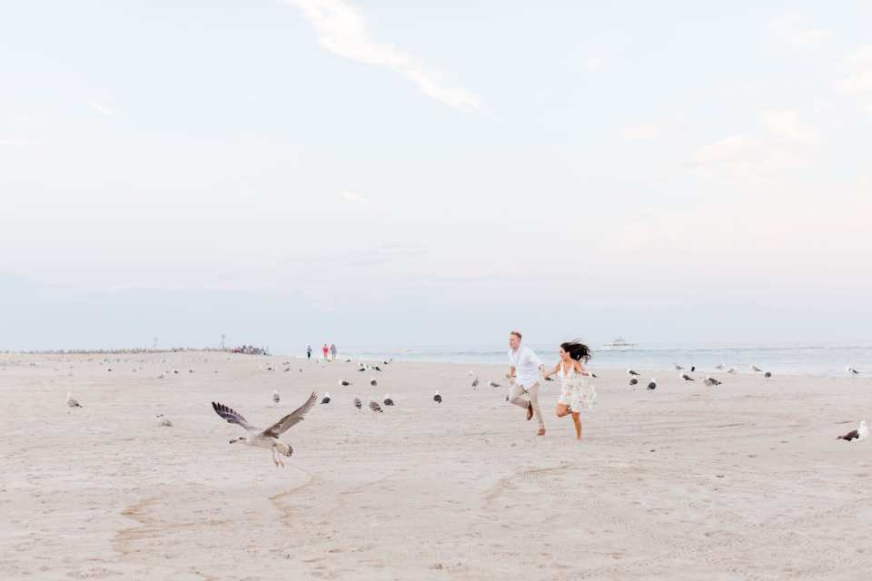 Bride and Groom to be running on the beach in Point Pleasant, with the birds flying round them