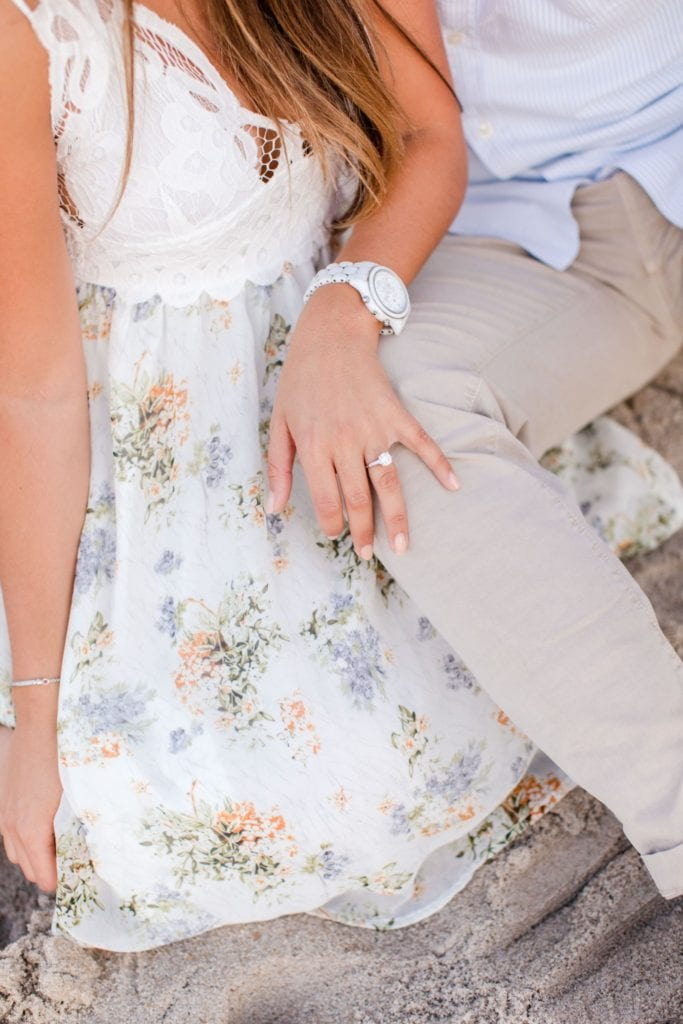 Bride to be sitting next to her groom to be on the sand, engagement ring from Ocean of Diamonds highlighted