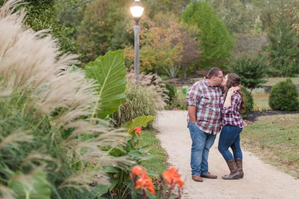 Wide angle photo of the engaged couple in their flannel shirts and jeans, kissing on a path that is winding amongst the foliage