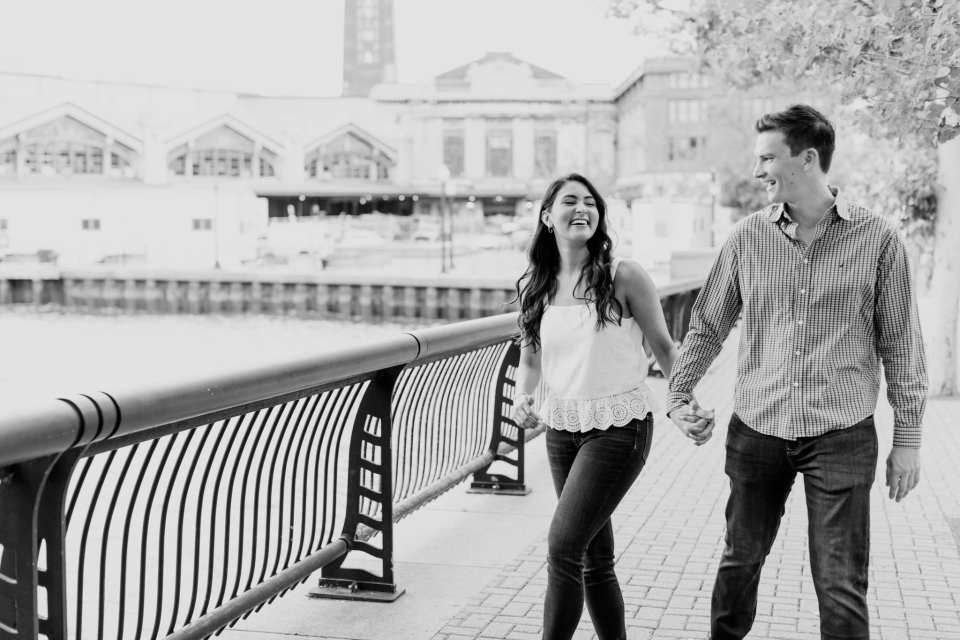 Black and white shot of the couple laughing while walking along the waterfront in Hoboken, New Jersey, the Hoboken train station in the distance