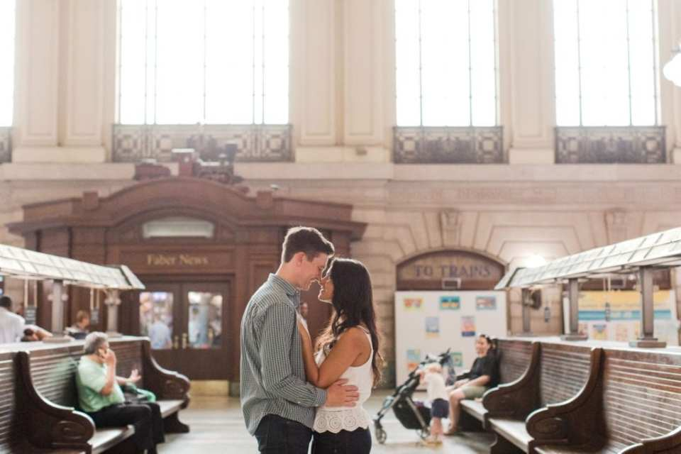 Half shot of the bride and groom to be with their foreheads together, gazing into one anothers eyes in the middle of the Hoboken train station by New Jersey wedding photographer
