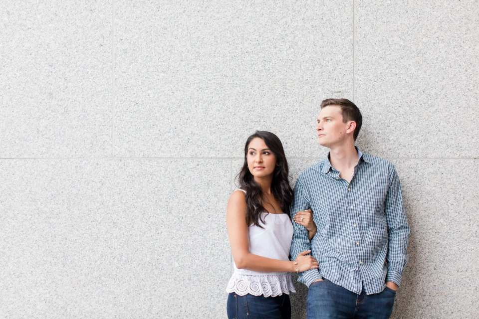 Casual photo of the engaged couple leaning against a wall, he in a shirt by Nautica, jeans by Banana Republic, she in a top from J.Crew, jeans by Madewell