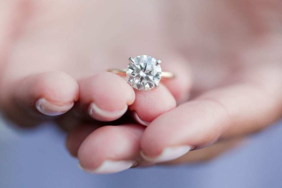 Round solitair diamond engagement ring on a gold band by David S Diamonds in the hands of the bride to be