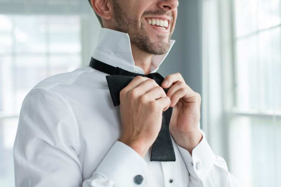 Close up of the groom tieing his bowtie