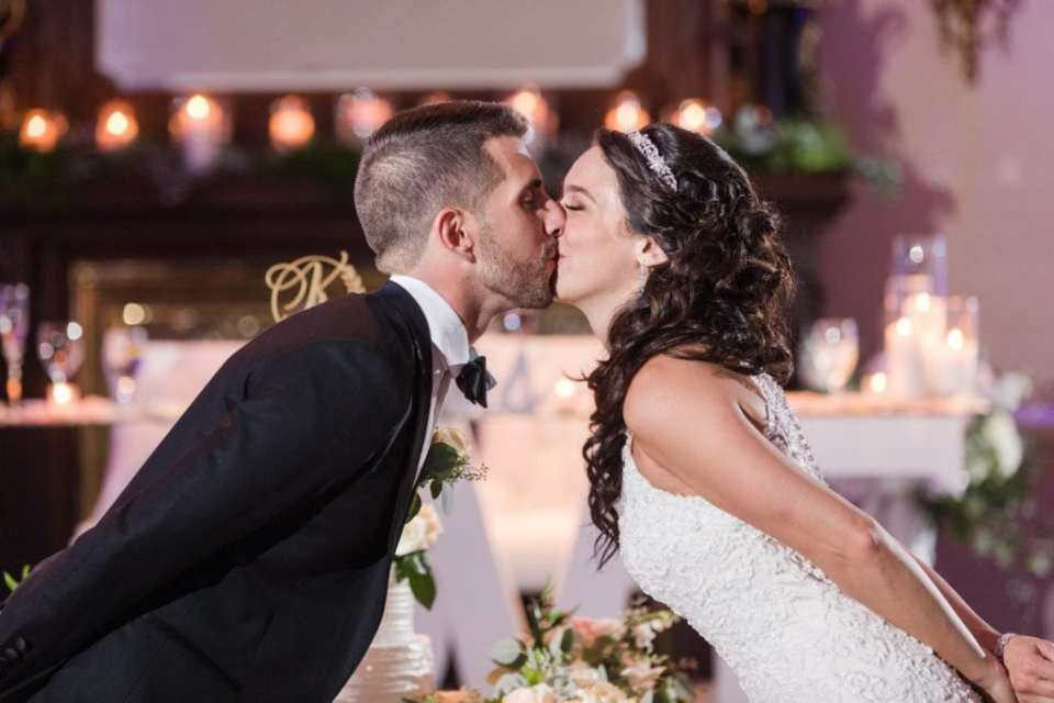 Bride and groom kissing while leaning into one another, hands behind each other at the Palace at Somerset Park wedding