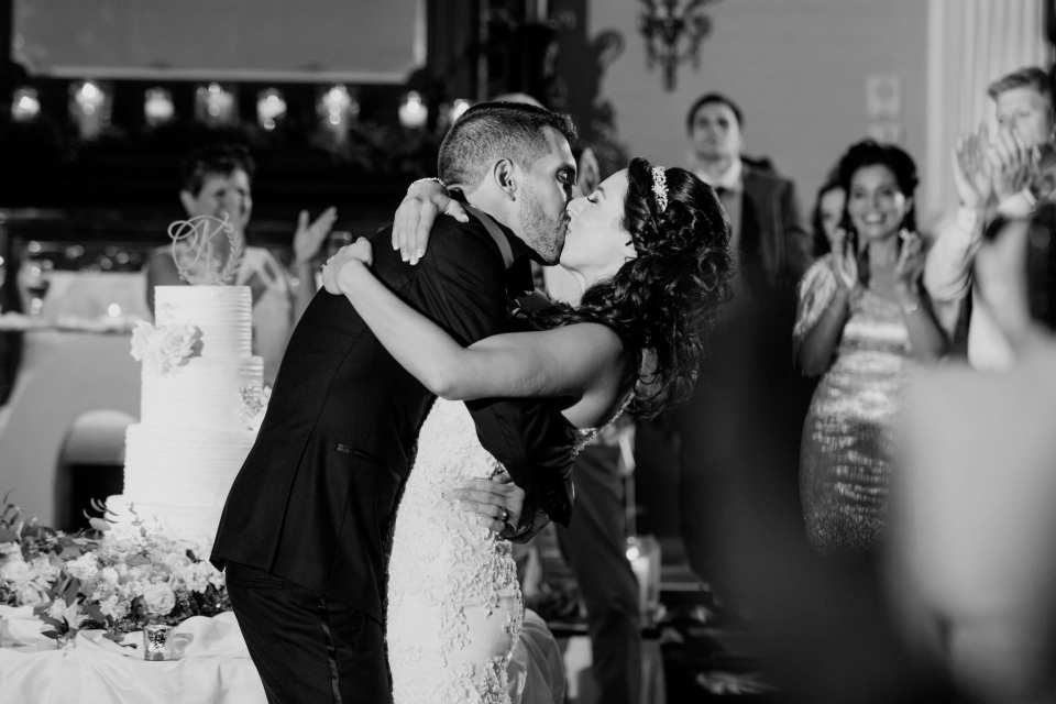 Black and white photo of the groom kissing his bride while slightly dipping her
