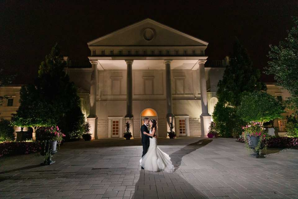 Wide angle nighttime portrait of bride and groom outside of the Palace at Somerset Park facing each other, his arms around her waist, her arms on his forearms