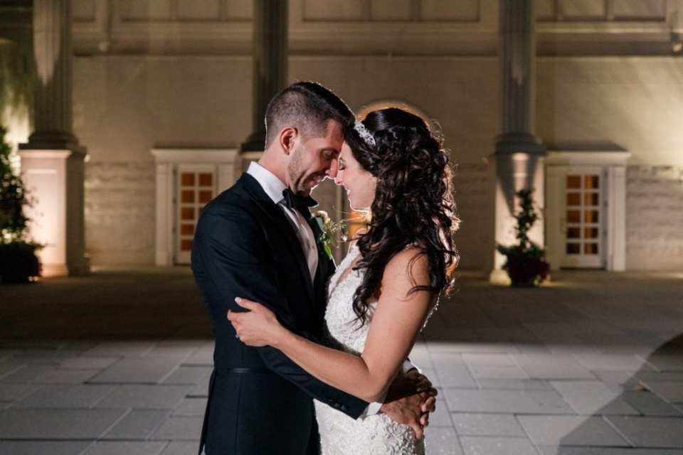 Nighttime portrait of bride and groom outside of the Palace at Somerset Park facing each other, foreheads together, his arms around her waist, her arms on his forearms