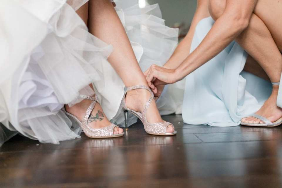 The bride being helped into her Jimmy Choo sparkly heels