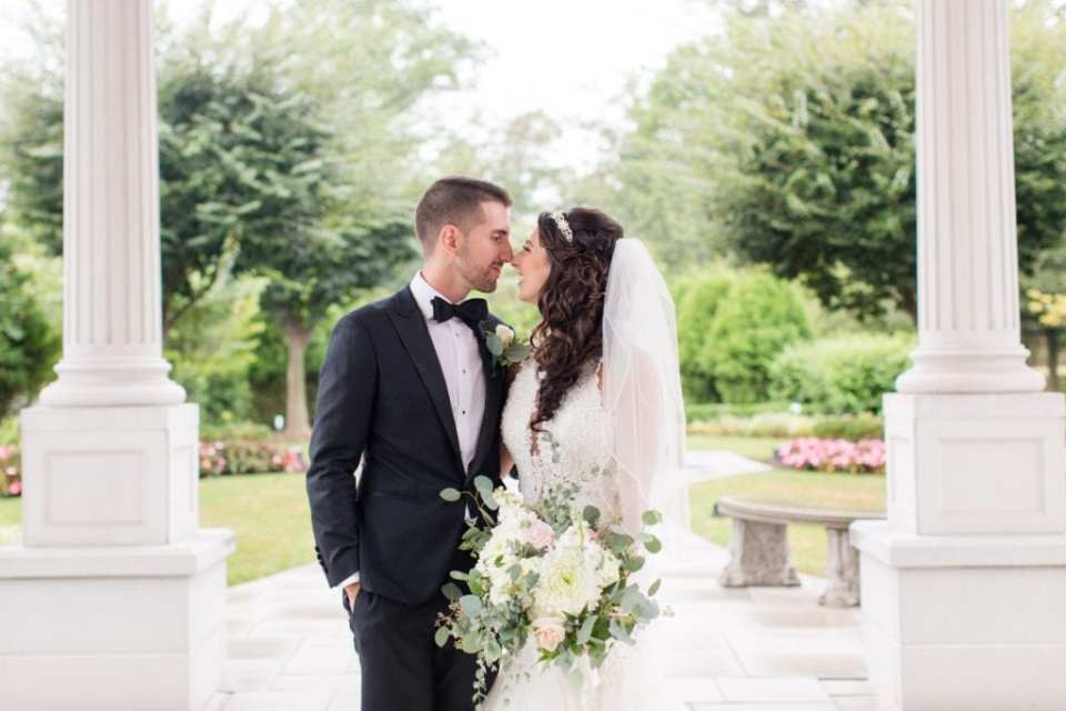 Bride and groom nose to nose, arms around one another's waists, the palace at somerset park wedding photo